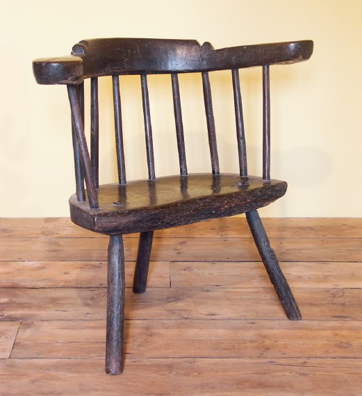 An archetypal yoke-back, in oak, with an armrest made from a single naturally bent branch, which is shaped on the top and terminates in large circular handrests. The seat is 10cm (3in)thick. Such chairs were used alongside the hearth, the low legs enabling the occupant to sit below the smoke level. The painted finish is worn back into the reddish timber and the resultant surface has a natural glow. Cardiganshire, circa 1720 -1760.Author's Collection.