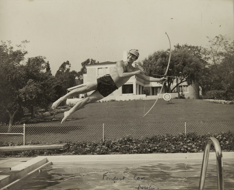 Photograph of David Niven jumping into swimming pool