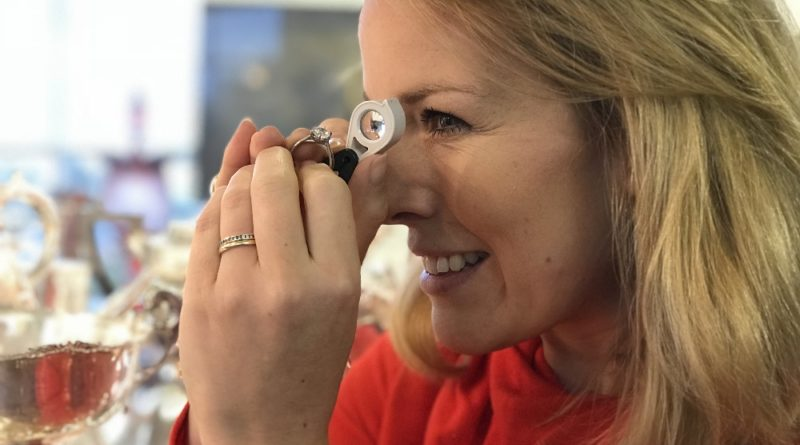 Auctioneer Christina Trevanion inspecting a solitaire ring